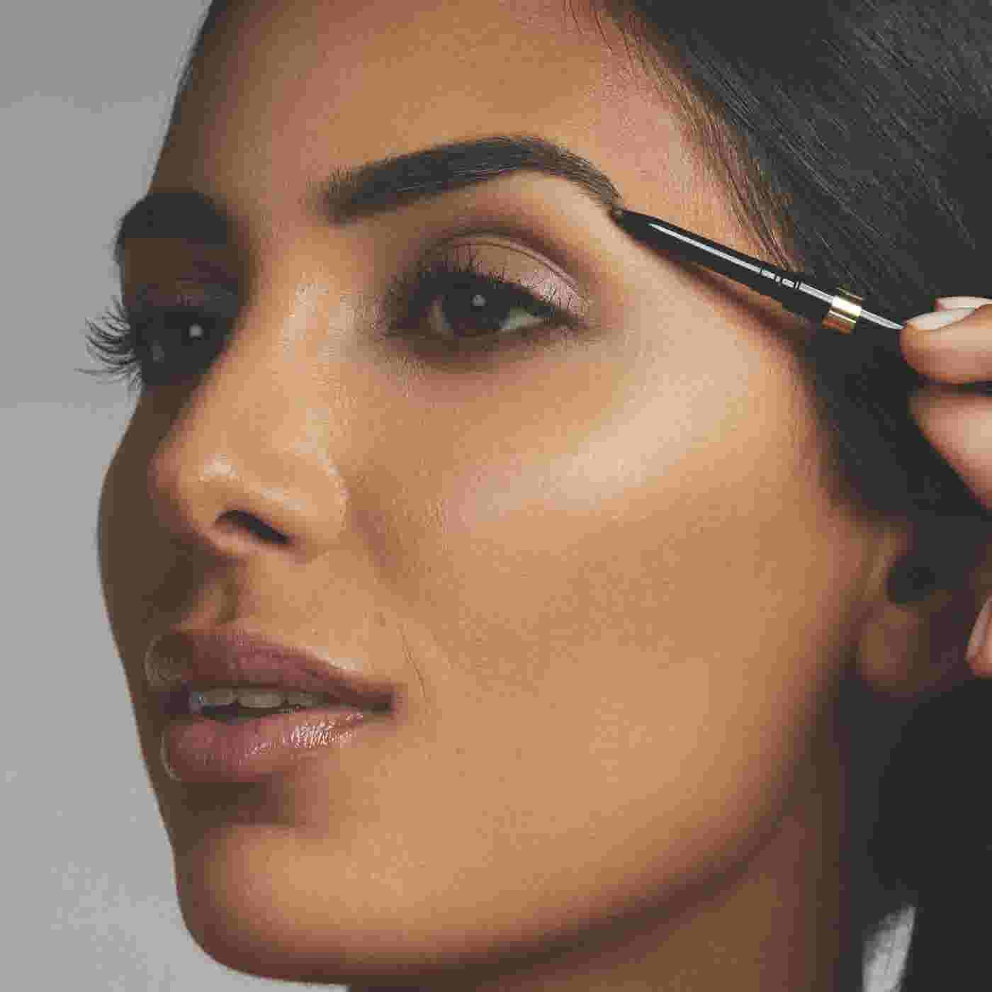 Model filling brows with Max Factor Brow Shaper Eyebrow Pencil
