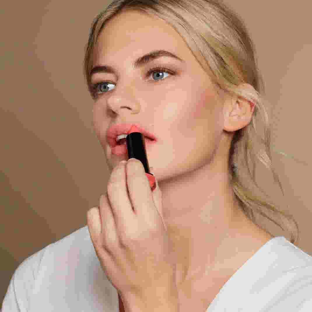 Model applying pink Max Factor lipstick