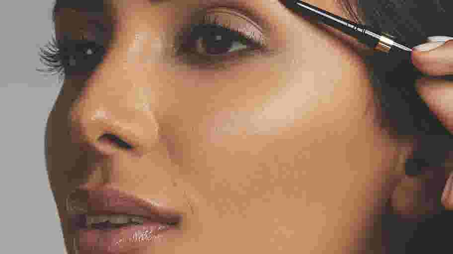 Model showing how to do eyebrows with Max Factor brow pencil