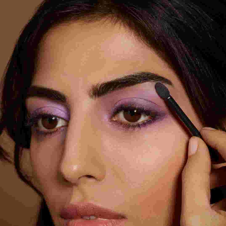 Model applying purple eyeshadow by Max Factor.