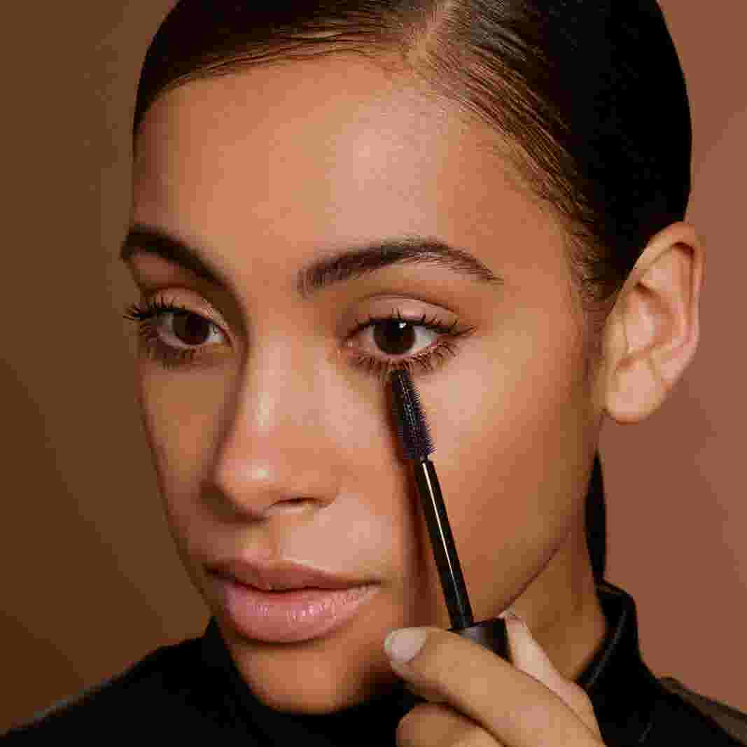 Model applying brown mascara to lower lashes. Look created by Max Factor.