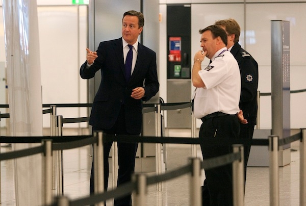 David Cameron talks to UK border agency officials in their control room during a visit to Heathrow. Picture: Getty