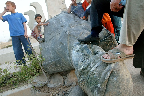 Children gather beside a toppled statue of Saddam Hussein as two men place their feet on the head to pose for a friend taking photographs April 14, 2003 in Bagdhad, Iraq.  (Photo by Mario Tama/Getty Images)