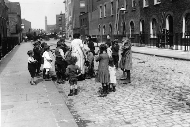 A woman talking to a group of children playing on the street in London. Image: Topical Press Agency/Getty Images