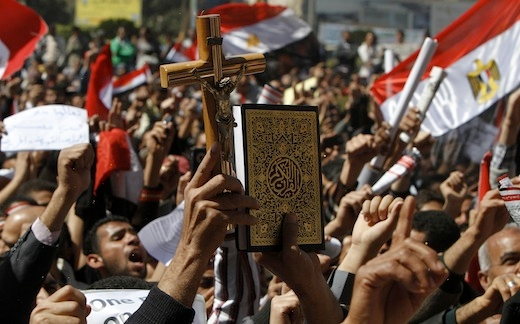 An Egyptian holds a cross and the Koran,