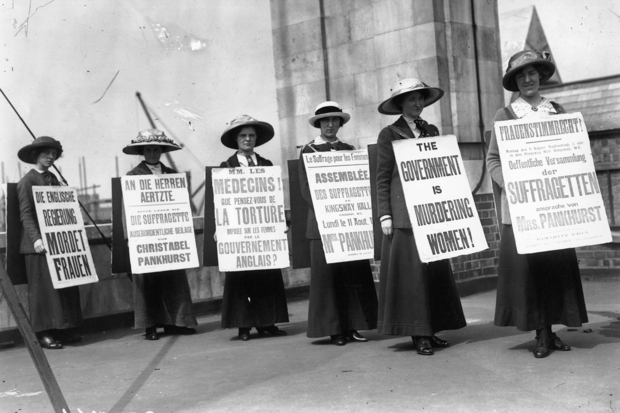 A group of suffragette women demonstrating in 1914 with placards in English, French and German (Photo: Topical Press Agency/Getty)