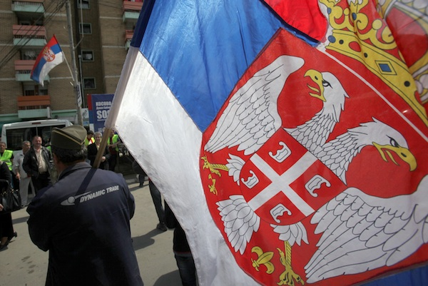 A protestor carries a Serbian flag at a protest against the recognition of Kosovo as an independent state. Image: PA
