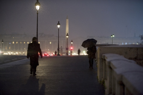 People walk on the snow-covered Pont de