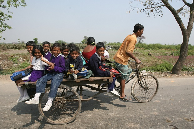 A group of Indian school children rides a cycle van to reach school near Kolkata. A reminder of how far India has yet to travel. (DESHAKALYAN CHOWDHURY/AFP/Getty Images)