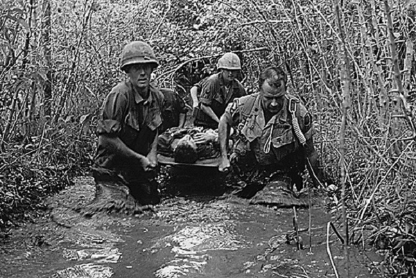 US soldiers carry a wounded comrade through a swampy area during action in Vietnam in 1969. NATIONAL ARCHIVES/AFP/GettyImages