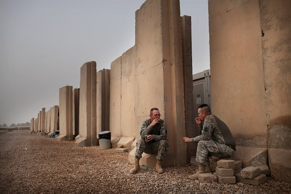 Soldiers take a cigarette break at base Kalsu on July 17, 2011 in Iskandariya, Babil Province, Iraq. (Photo by Spencer Platt/Getty Images)
