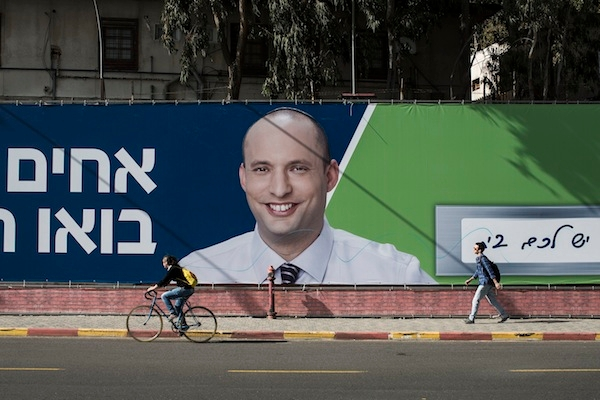 People pass by campaign posters of chairman of the far-right Habayit Hayehudi party Naftali Bennett ahead of the national elections. Picture: Getty