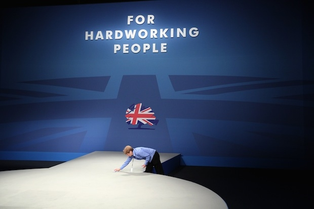 A woman cleans the stage ahead of David Cameron's speech yesterday. Picture: Getty