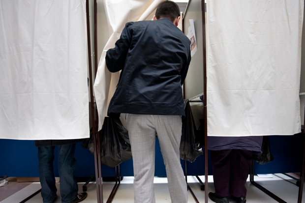 A man enters a voting booth before casti