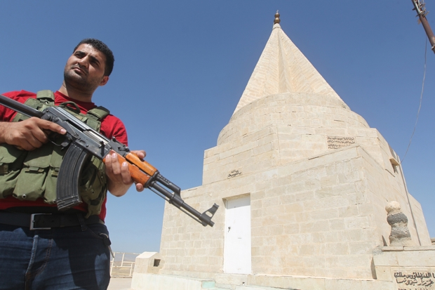 An Iraqi Yazidi fighter stands guard outside a shrine (Photo: Ahmad Al-Rubaye/Getty)