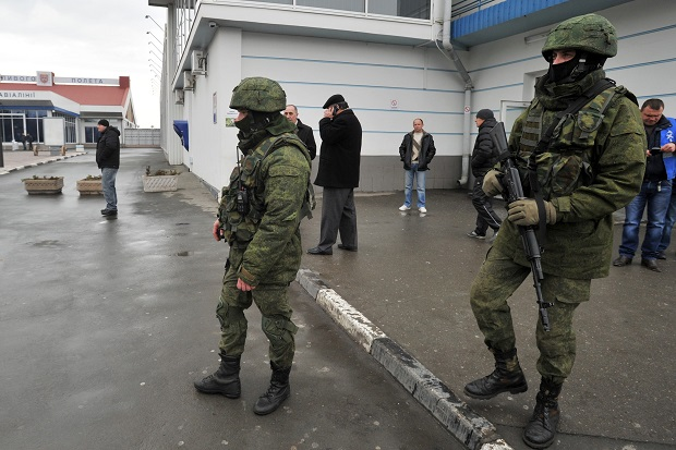 Unidentified armed men patrol outside of the Simferopol airport. (GENYA SAVILOV/AFP/Getty Images)