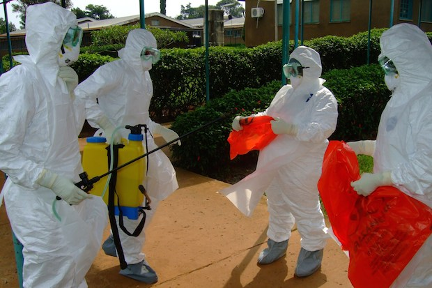 Officials from the World Health Organization wearing protective clothing as they prepare to enter a hospital in Uganda. Image: ISAAC KASAMANI/AFP/Getty Images