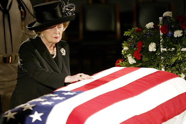 The late Margaret Thatcher touches the flag draped coffin of former President Ronald Reagan on 09 June 2004. (STEPHEN JAFFE/AFP/Getty Images)