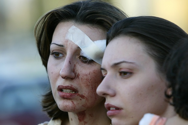 Injured Iraqi Christians wait outside a hospital after treatment following explosions near two Baghdad churches on 1 August 2004. (AHMAD AL-RUBAYE/AFP/Getty Images)