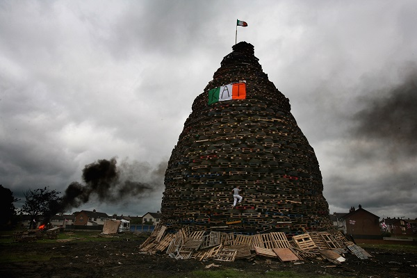 A boy climbs on a bonfire made from pallets and old tyres on the Loyalist Ballycraigy estate in Antrim, near Belfast. (Image: Getty)