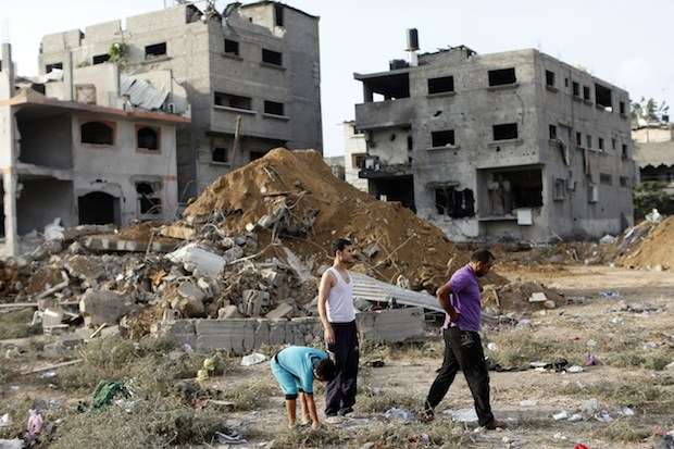 Palestinian men search through the rubble of buildings following an Israeli air strike, that killed 18 people of the same family in Gaza City, on July 13, 2014. Image: THOMAS COEX/AFP/Getty Images