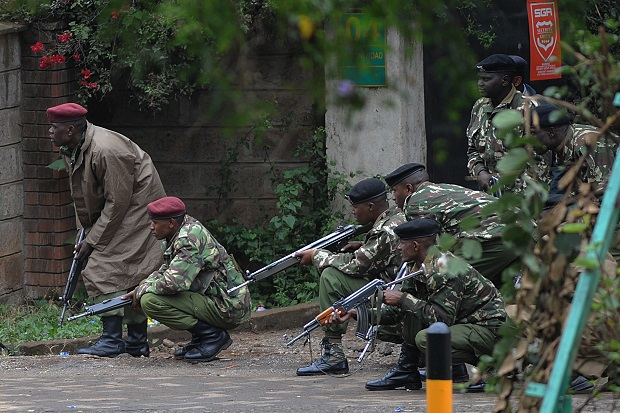 Armed policemen take cover outside the Westgate Mall in Nairobi, which has been occupied by murderous Islamists. (SIMON MAINA/AFP/Getty Images)