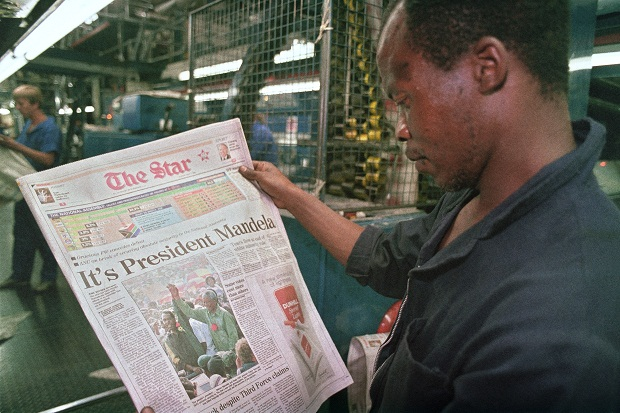 A worker in Pretoria reads news of Nelson Mandela's historic victory in 1994. (PHILIPP LITTLETON/AFP/Getty Images)