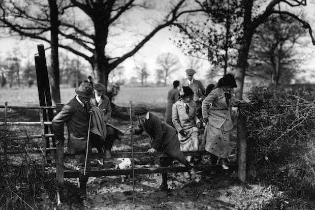 8th April 1914:  Members of the Crowhurst Otter Hounds climb over a gate during a hunt in Edenbridge, Kent.  (Photo by Topical Press Agency/Getty Images)