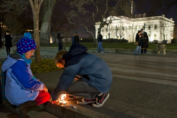 People gather outside the White House for a vigil after yesterday's shootings. Image: Getty