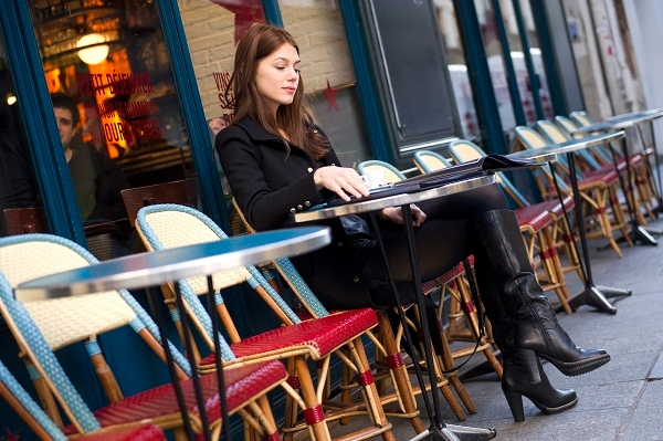 Ioana Timoce sits at a cafe terrace with her new book. Image: LIONEL BONAVENTURE/AFP/Getty Images