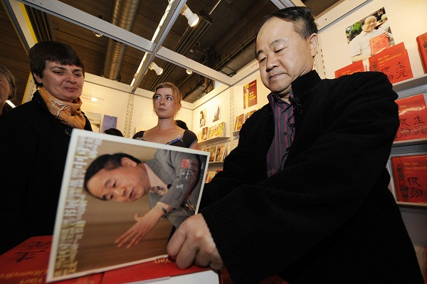 Chinese author Mo Yan autographs his boo
