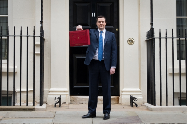 A slimmed-down George Osborne poses with the Budget. (LEON NEAL/AFP/Getty Images)