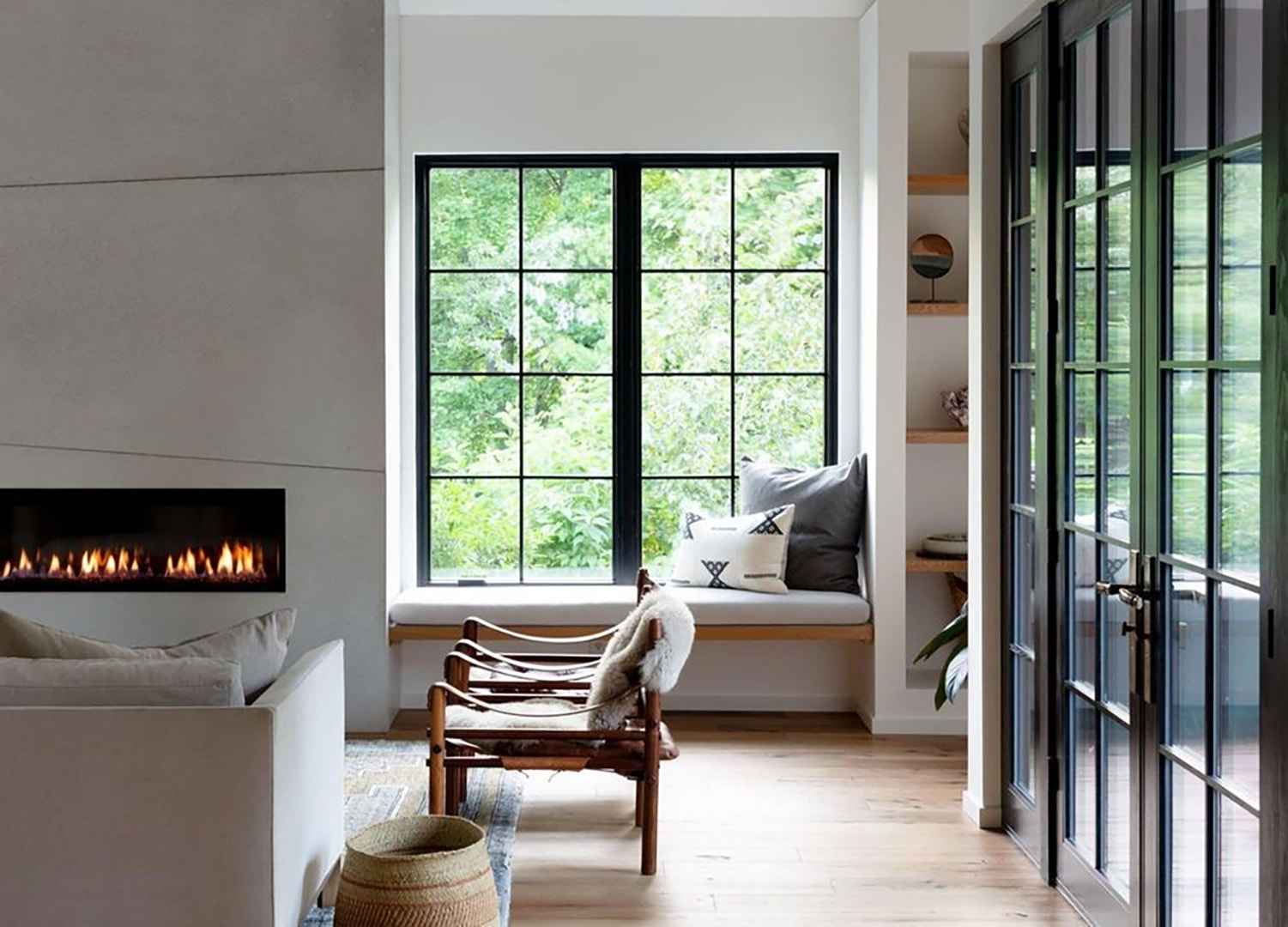 Two black casement windows open the living room to fresh air and offer seating area to warm up by the fireplace.