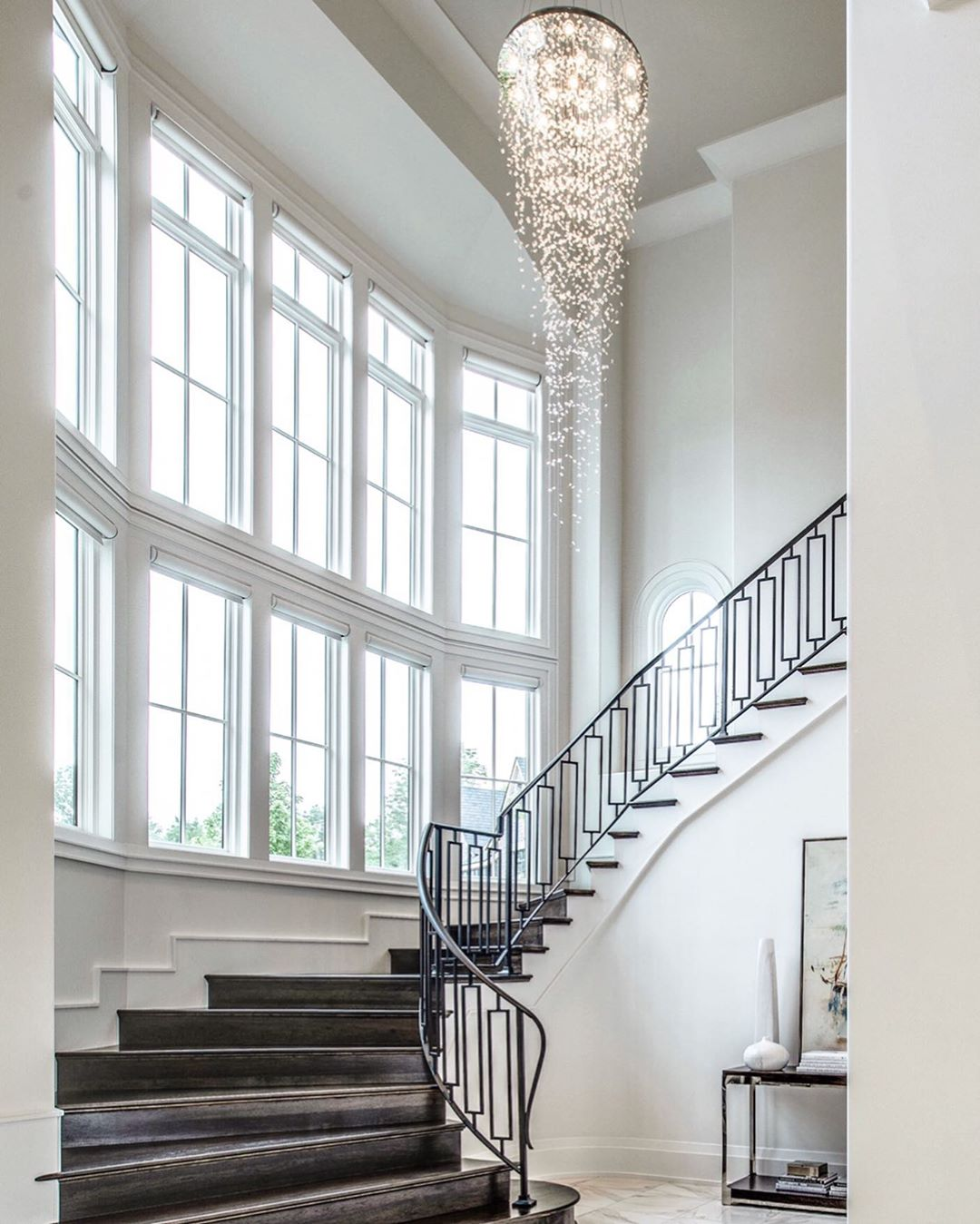 grand staircase overlooking two rows of white fixed windows bringing in natural light