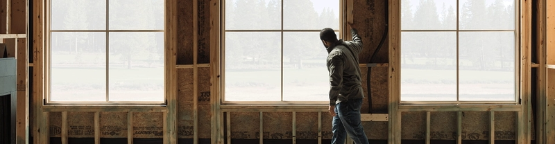 contractor standing near the windows of a new home under construction
