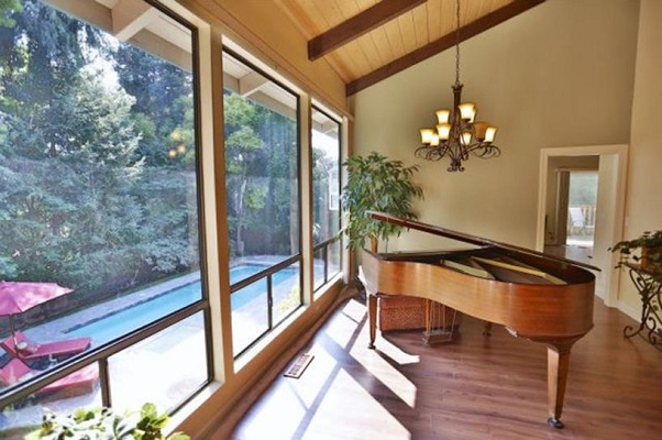 Large old windows in living room with grand piano