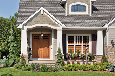 wood craftsman entry door on home exterior three hung windows with wood shades