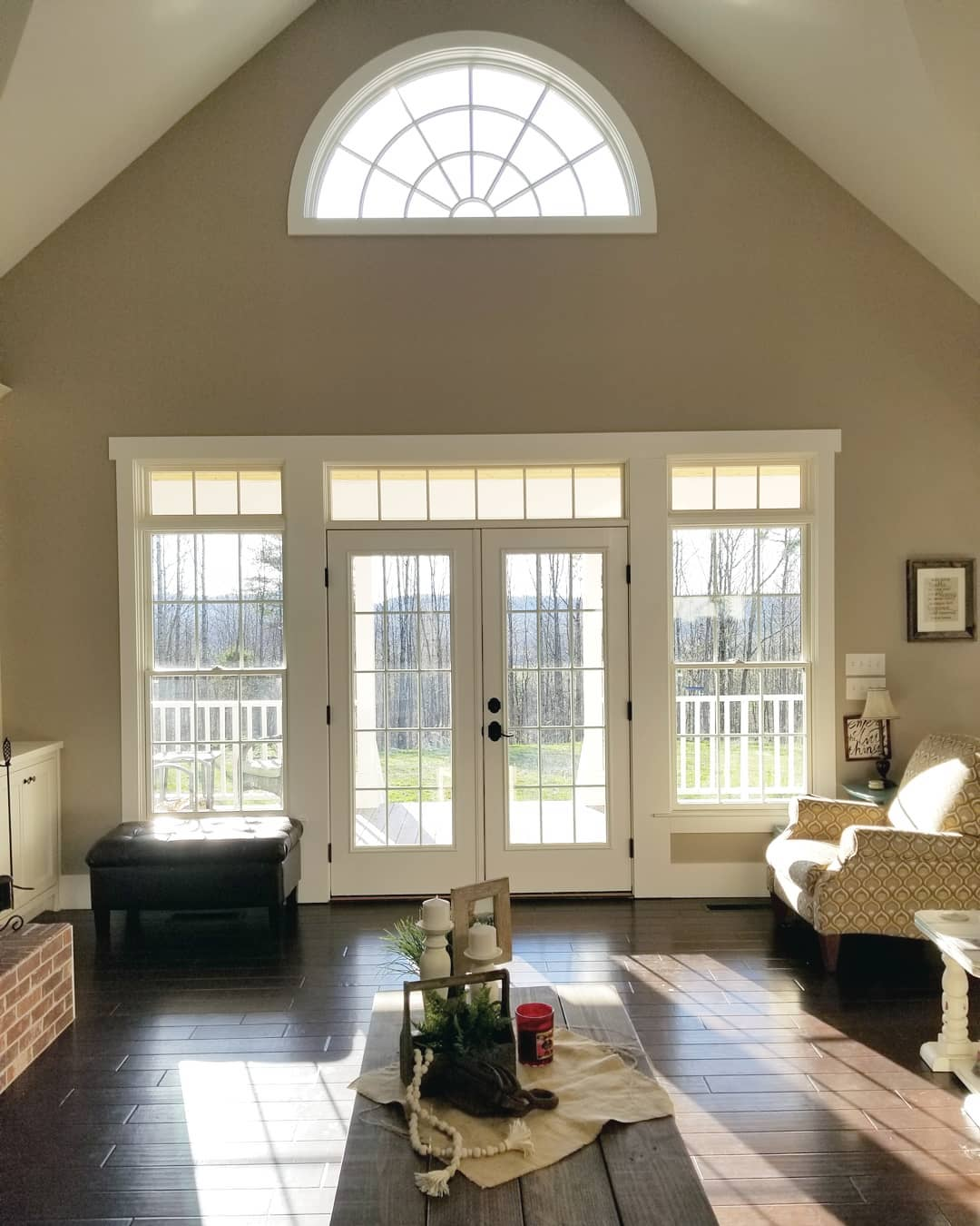 traditional living room with white french doors surrounded by white windows on either side