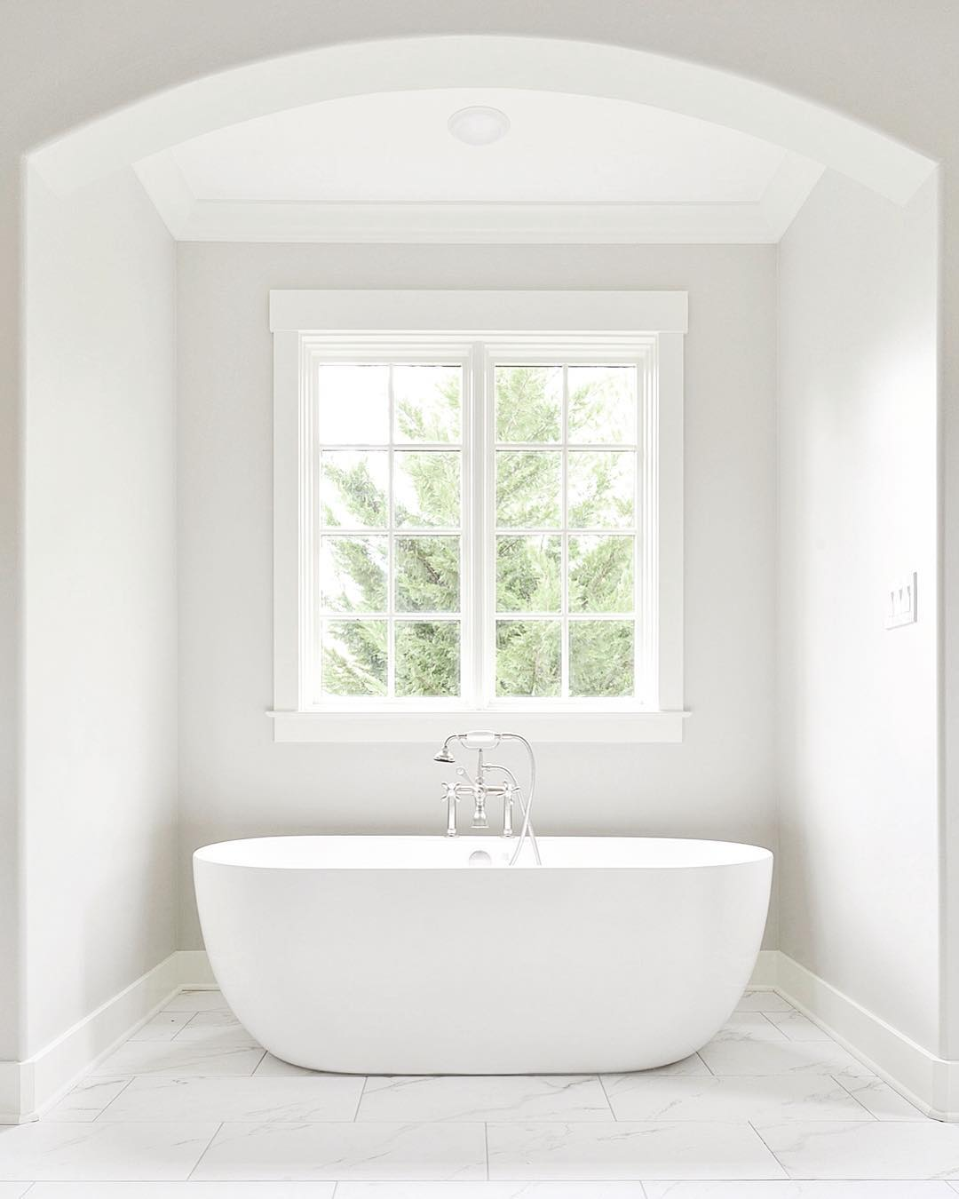 White on white bathroom with large casement window over freestanding tub