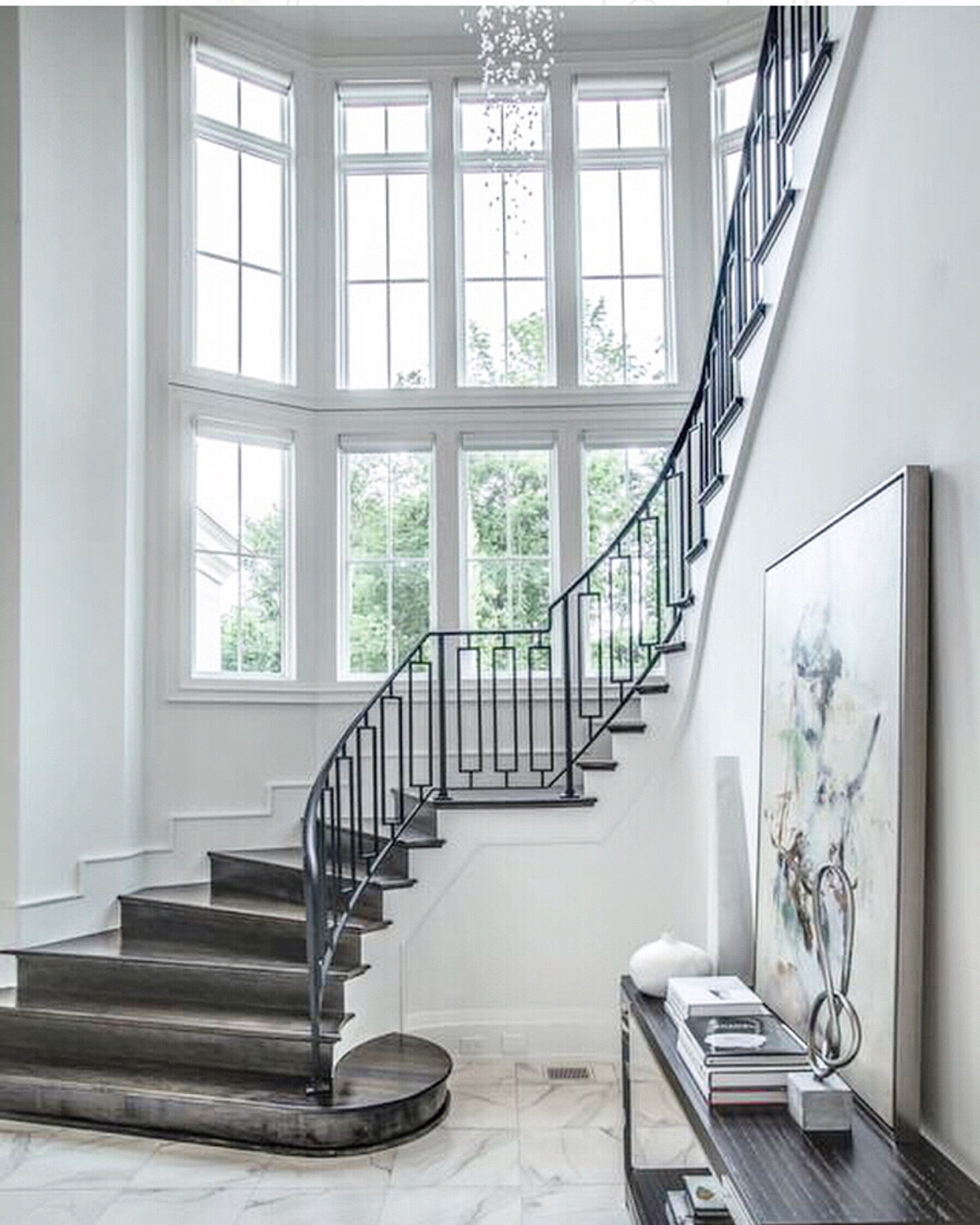 curved wall full of white windows with a grand carpeted staircase