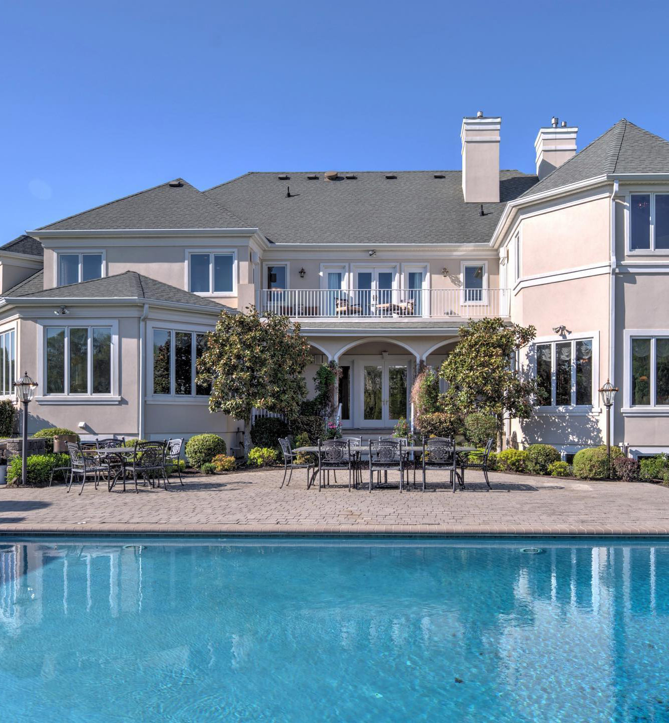 A large house with white casement windows, hinged patio door and an outdoor seating area.