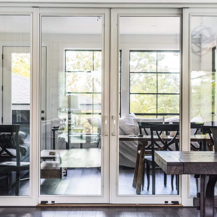 Sliding patio door with minimal white frame and large expanse of glass seperates dining room from backyard