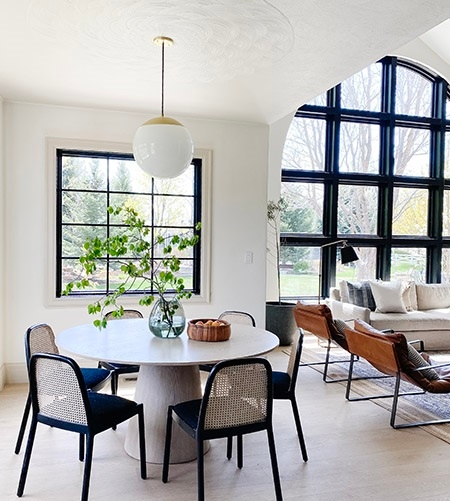 Breakfast nook with black window overlooking living room with large arched picture window