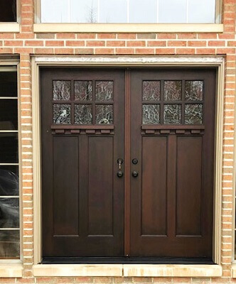 Craftsman style brown double door on a brick home