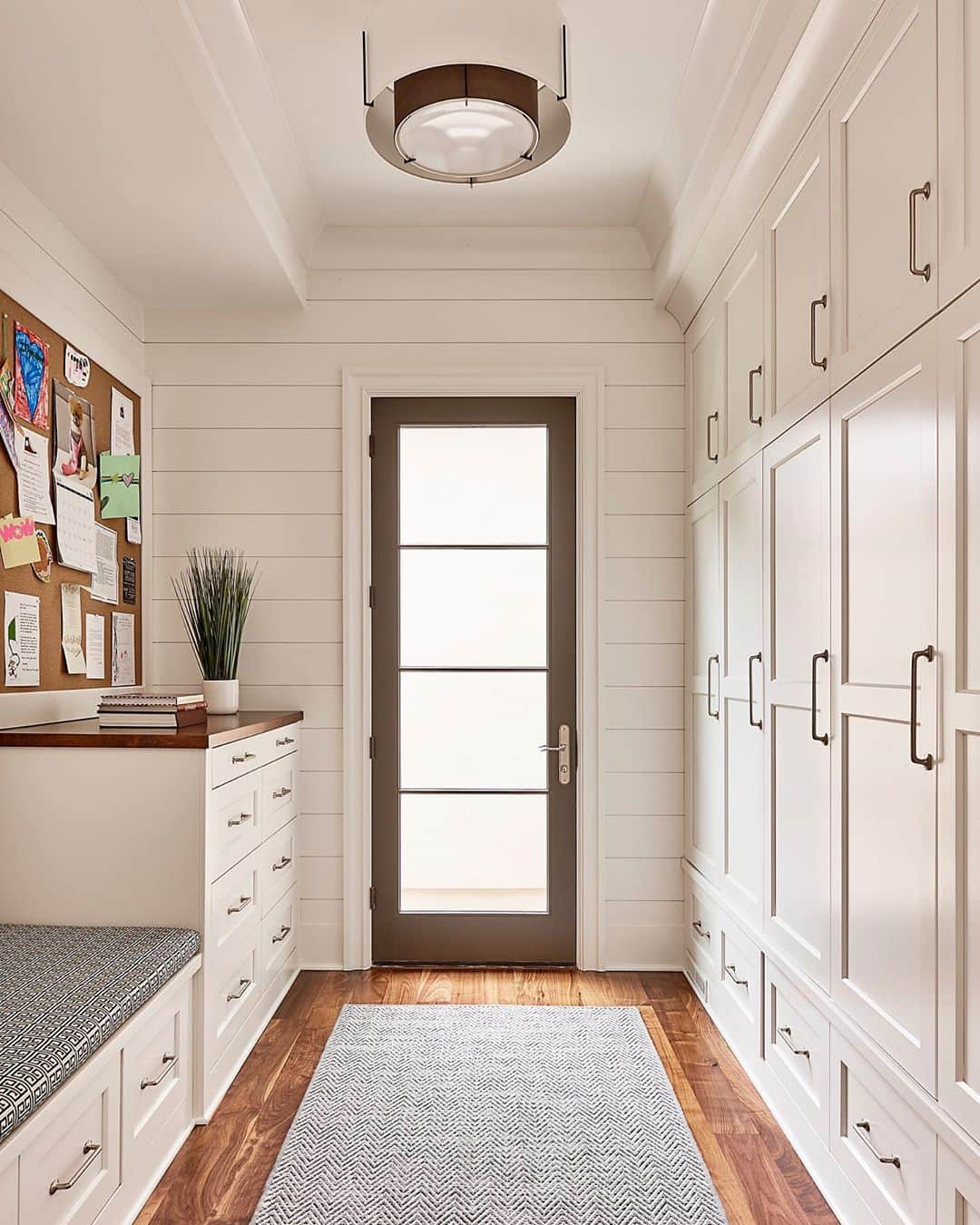 contemporary style mudroom with a wall of white cabinets leading to hinged glass patio door