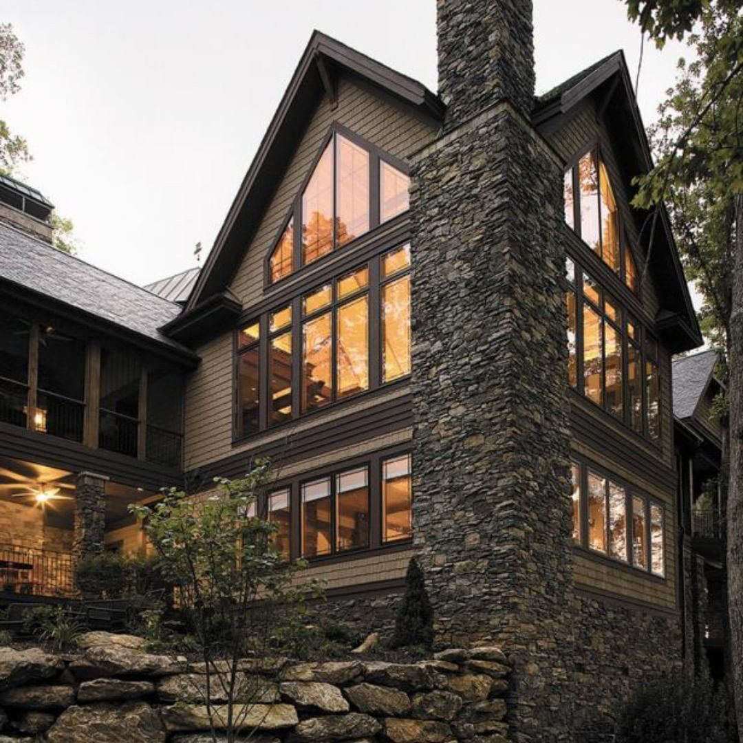 Rustic cabin with tall walls of windows shaped with triangle shaped windows to match roofline