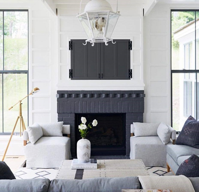 white walls black fireplace with large black double-hung windows on either side in contemporary living room