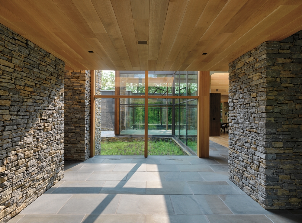 Hallway with stone walls on either side, wood plank ceiling, and wall of picture windows ahead