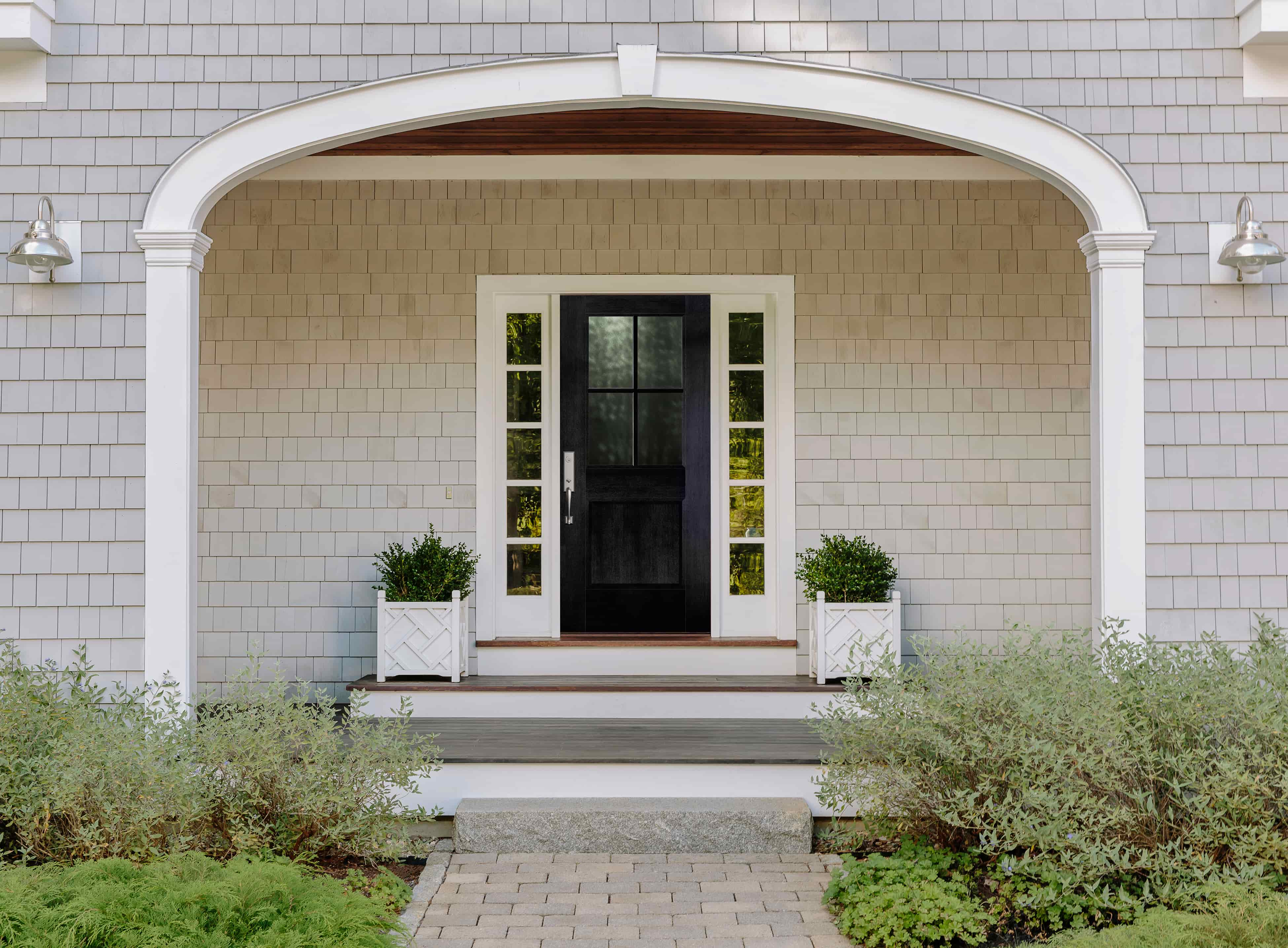 Black front door with white sidelights under arched farmhouse porch