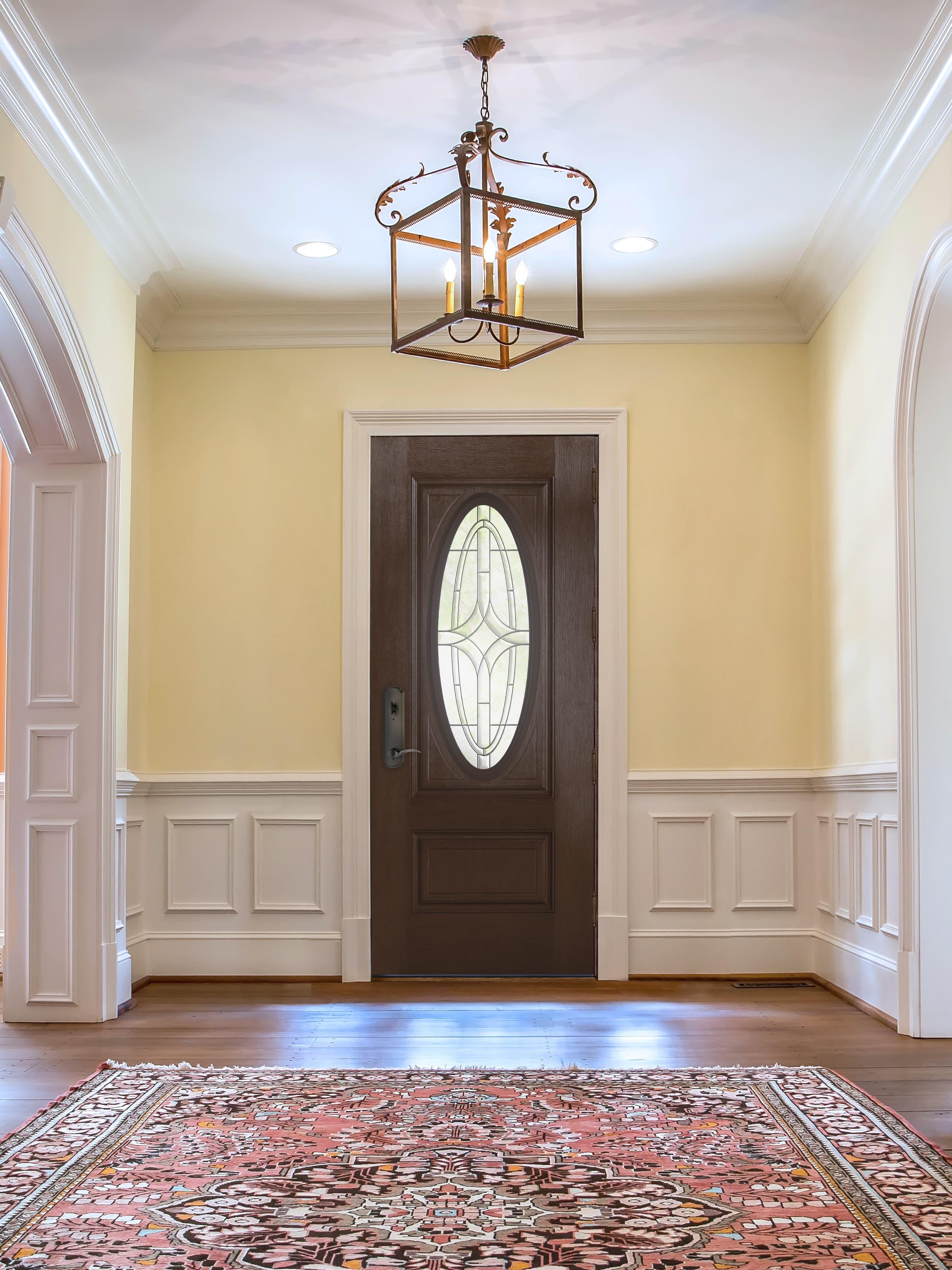 Brown front door with ornate glass in elegant entryway